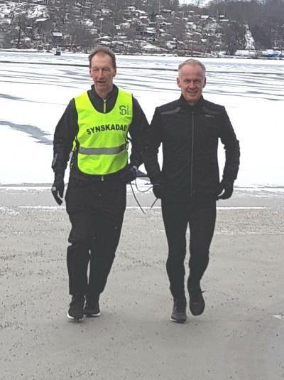 Stefan är ute och löptränar med en kund i ett snötäckt landskap. Stefan är helt klädd i svart, hans tränarkompis också klädd i svart men har en neongul väst på sig där det står synskadad på. Emellan sig har de ett band som de håller i.