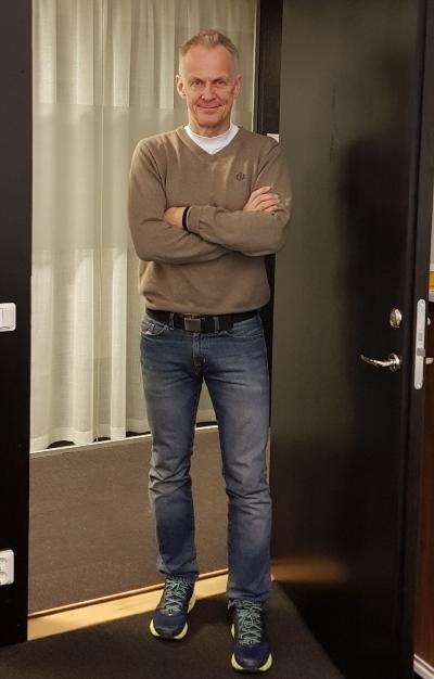 Stefan står i dörröppningen till kontoret. Han är klädd ivit T-shirt och beige tröja samt blå jeans, han har armarna i kors och ler.